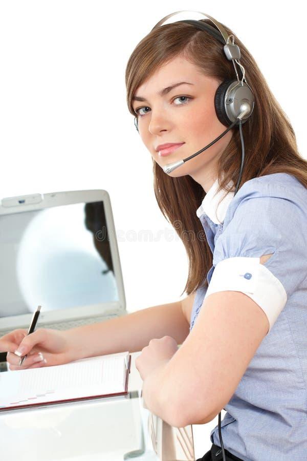 Vrouw in bureau met hoofdtelefoon stock foto's