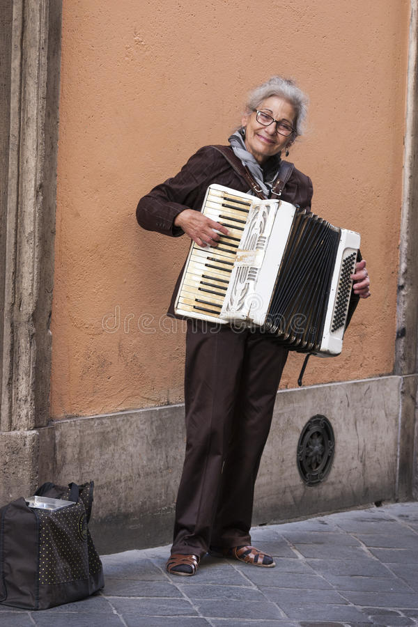 Vrouw busker het spelen harmonika De witte kunstenaar van de haarstraat stock fotografie