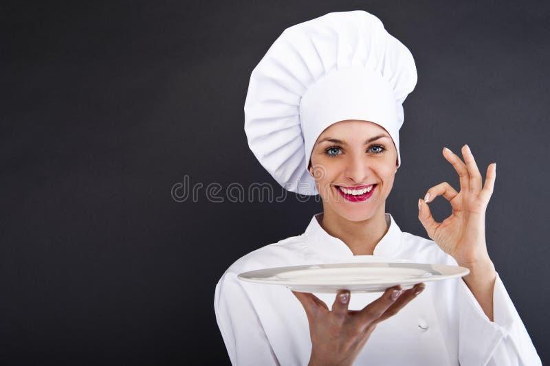 Vrouw cheff over donkere backgrund stock afbeeldingen