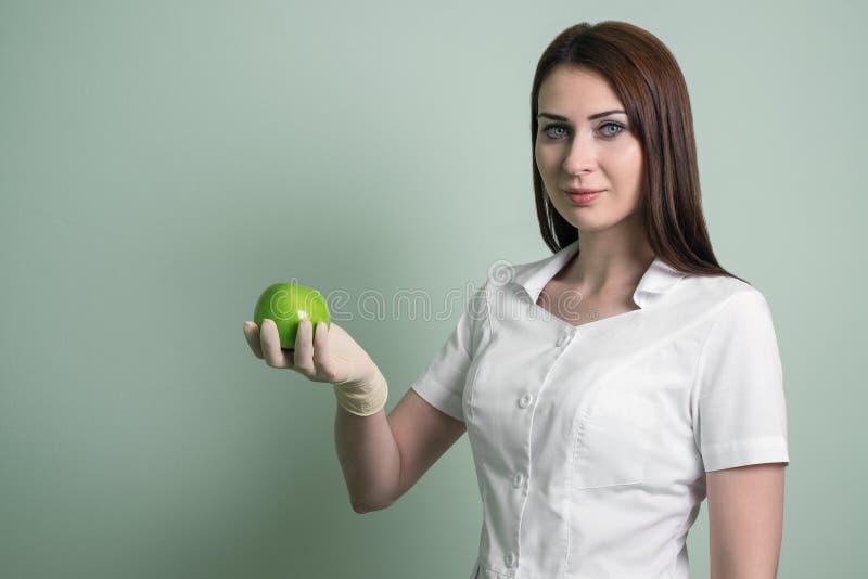 Vrouw de arts toont groen Apple Hygiëne en gezondheid van tanden stock foto's
