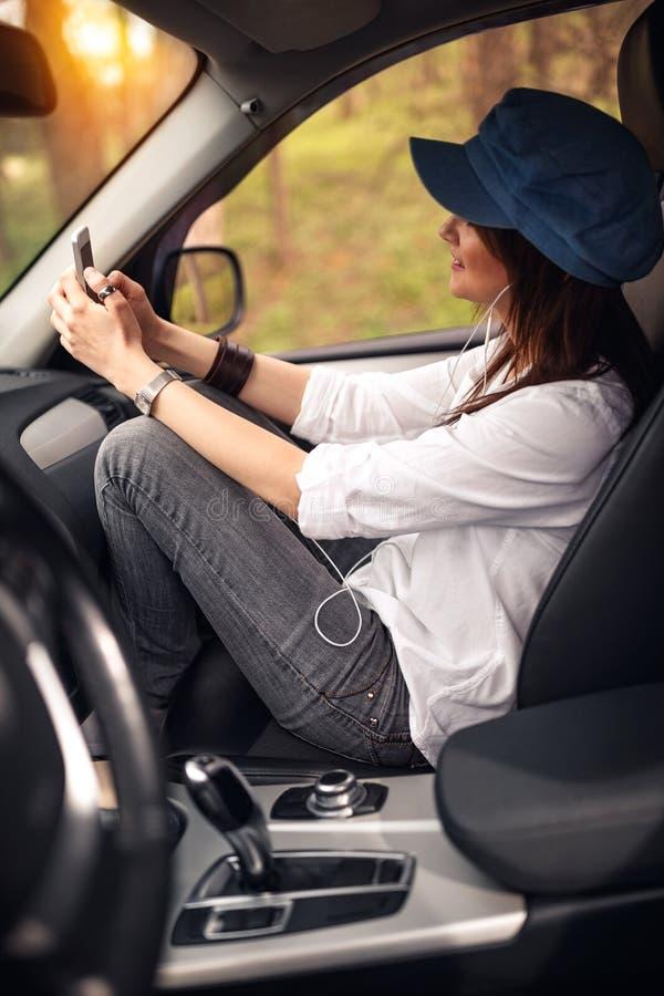 Vrouw in de auto Glimlachend meisje die aan muziek op uw smartp luisteren stock fotografie