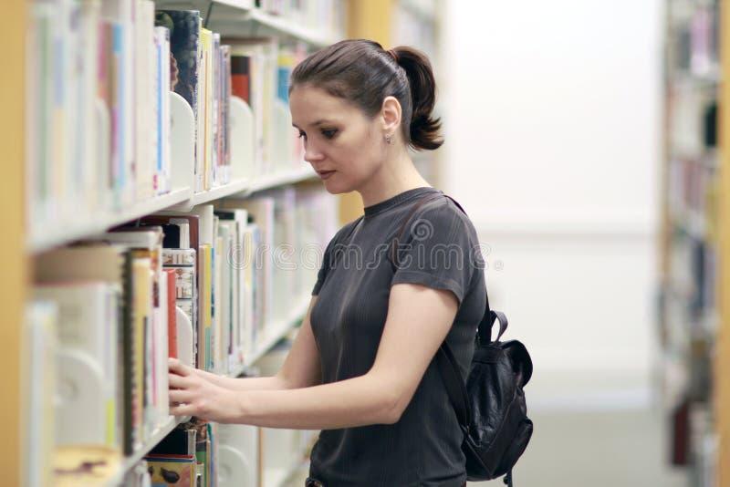 Vrouw in de bibliotheek stock foto's