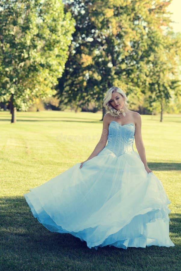 Vrouw in de blauwe kleding die van Tulle in het park dansen stock fotografie