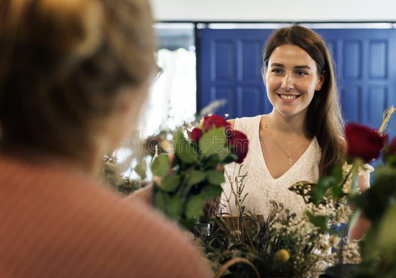 Vrouw in de bloemwinkel stock afbeelding