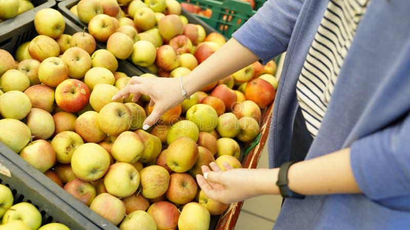 Vrouw in de fruitmarkt met in hand appel Vruchten en groenten Heel wat vruchten Opslagachtergrond Natuurlijk gezond voedsel stock fotografie