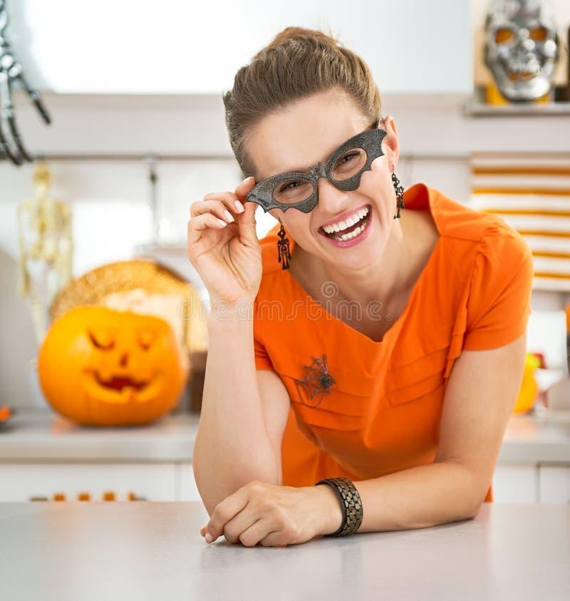 Vrouw in de glazen van de partijknuppel in de Halloween verfraaide keuken royalty-vrije stock foto