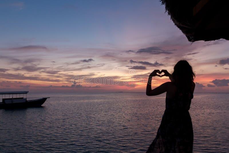 Vrouw in de hand van wittebroodswekenkaders in hartvorm, het kader van het vingerhart Zonsondergang over de oceaan royalty-vrije stock fotografie