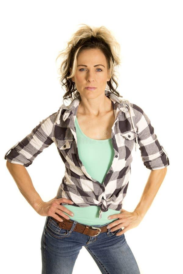Vrouw in de handen van het plaidoverhemd op ernstige heupen stock fotografie