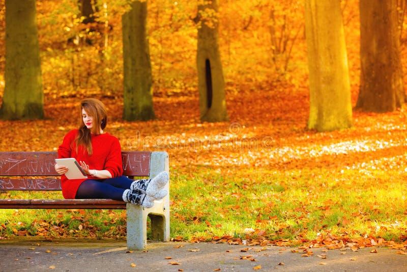 Vrouw in de herfstpark die de lezing van de tabletcomputer gebruiken stock foto's