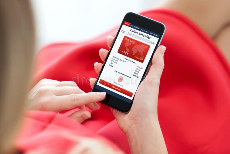Vrouw in de rode telefoon van de kledingsholding met app het online winkelen stock afbeelding
