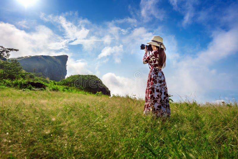 Vrouw de status op weide en het houden van camera nemen foto bij Phu-Chifa bergen in Chiangrai, Thailand reis concept royalty-vrije stock fotografie