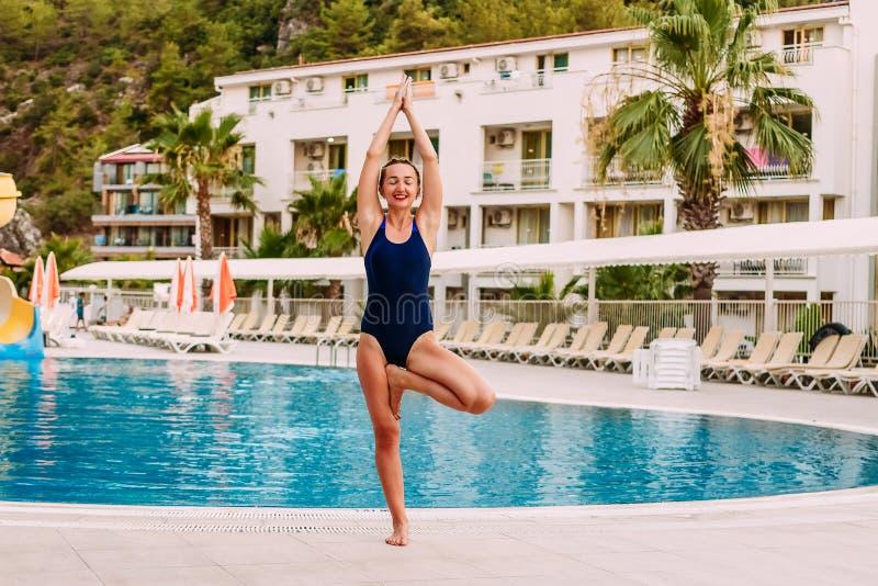Vrouw de status in stelt van een boom in yoga stock foto
