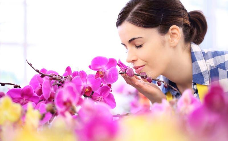 Vrouw in de tuin van bloemen, aanrakingen en geurenorchidee stock foto's