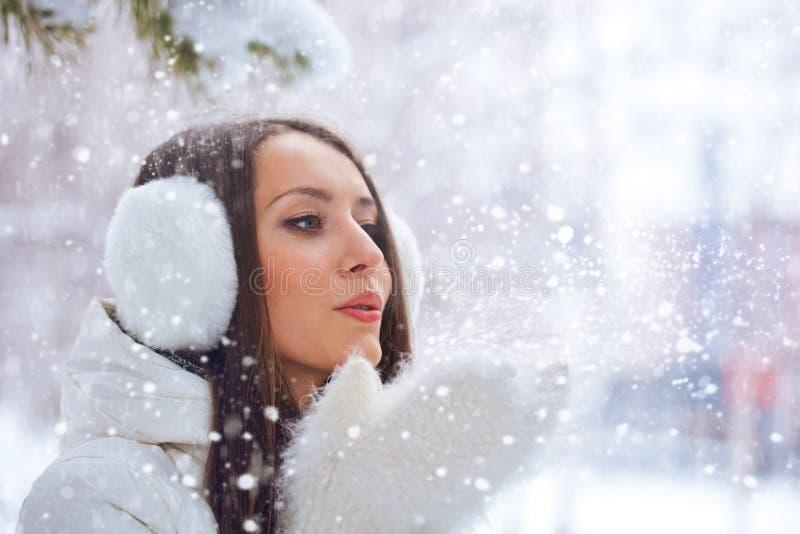 Vrouw in de winterpark die op sneeuw blazen stock afbeeldingen