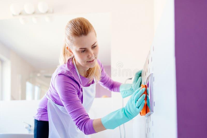 Vrouw in de witte drukknop van het schort schoonmakende toilet royalty-vrije stock afbeeldingen