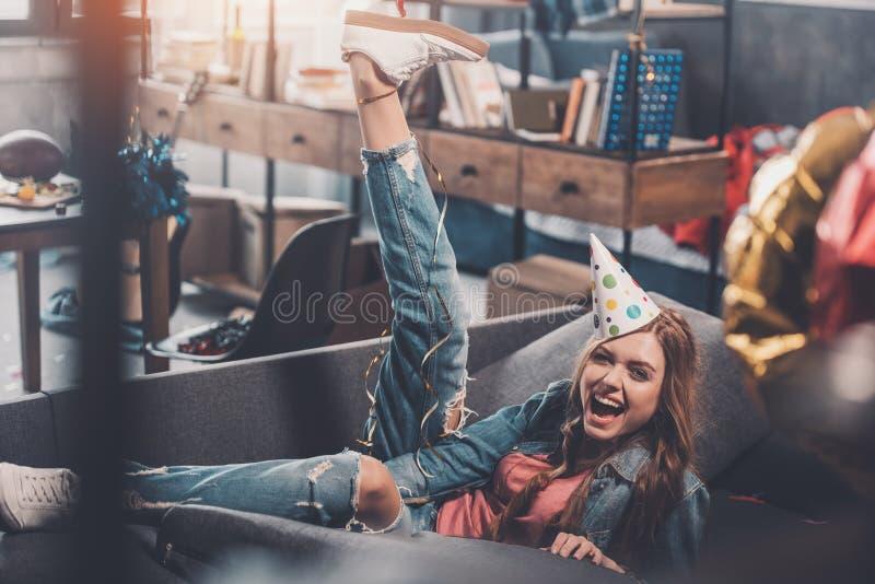 Vrouw in de zitting van de verjaardagshoed op bank in slordige ruimte na partij stock afbeeldingen