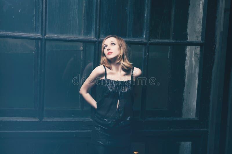 Vrouw dichtbij het venster royalty-vrije stock afbeeldingen