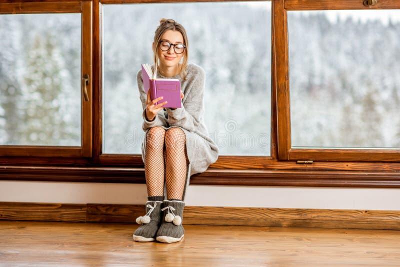 Vrouw dichtbij het venster tijdens de winter stock afbeelding