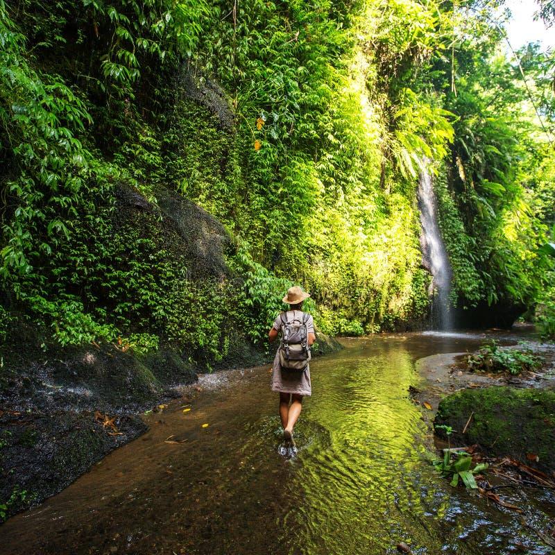 Vrouw dichtbij waterval op Bali, Indonesië stock foto's