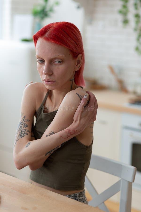 Vrouw die aan anorexie wat betreft haar schouders lijdt stock afbeelding