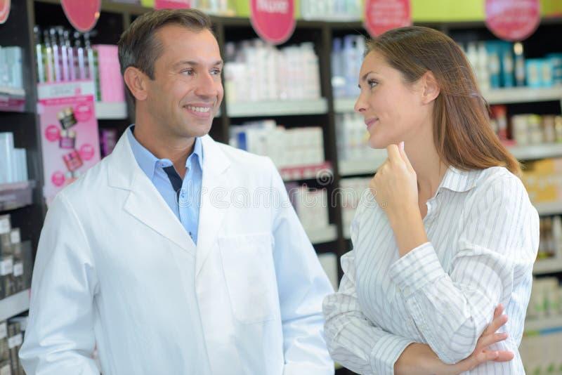 Vrouw die aan apotheker in drogisterij spreken stock fotografie
