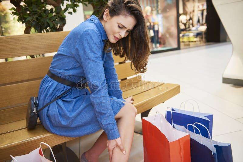 Vrouw die aan beenpijn tijdens het winkelen lijden royalty-vrije stock foto