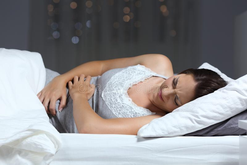 Vrouw die aan buikpijn in de nacht op het bed lijden royalty-vrije stock fotografie