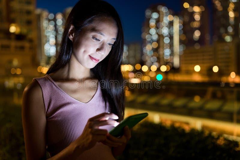 Vrouw die aan cellphone bij nacht werken royalty-vrije stock afbeelding