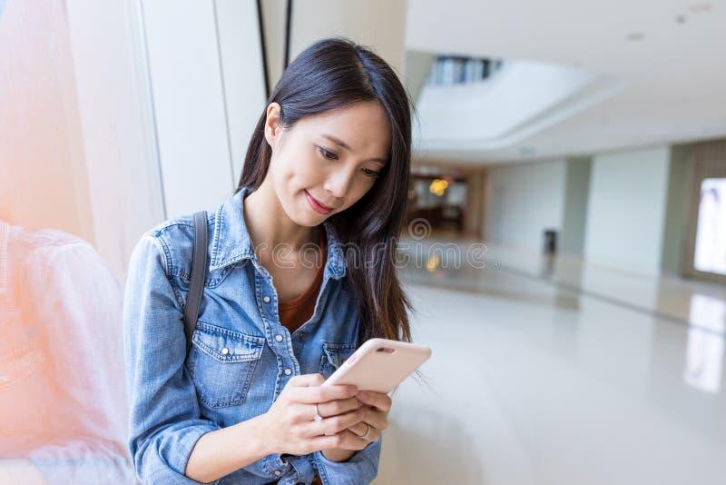 Vrouw die aan cellphone in winkelcomplex werken royalty-vrije stock fotografie