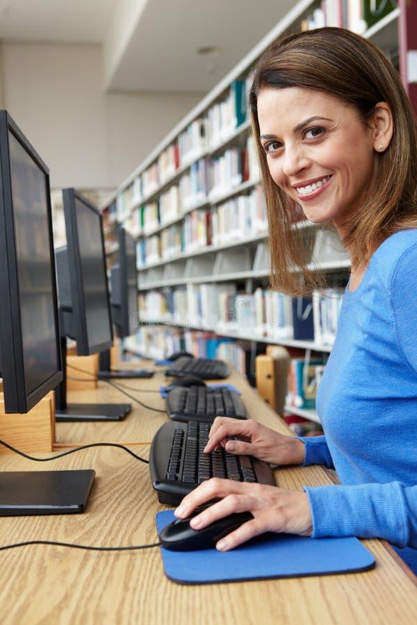 Vrouw die aan computer in bibliotheek werken royalty-vrije stock foto