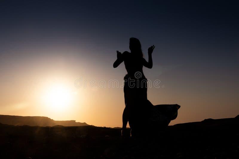 Vrouw die aan de beroemde Arabische buikdans dansen Met zonsondergang in de dorre woestijnvlakte van Namibe afrika angola royalty-vrije stock fotografie
