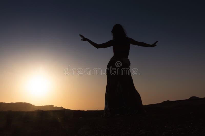 Vrouw die aan de beroemde Arabische buikdans dansen Met zonsondergang in de dorre woestijnvlakte van Namibe afrika angola stock foto's