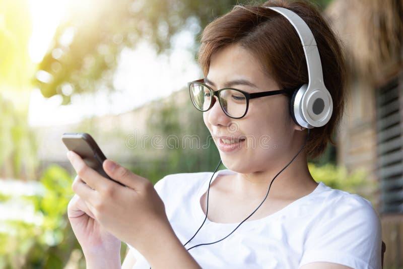 Vrouw die aan de muziek met hoofdtelefoon en slimme telefoon luisteren stock foto