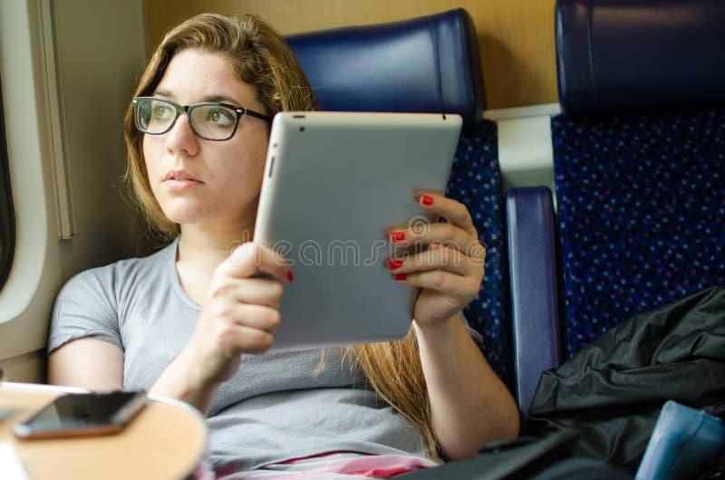 Vrouw die aan de trein met mobiele apparaten werken royalty-vrije stock afbeeldingen