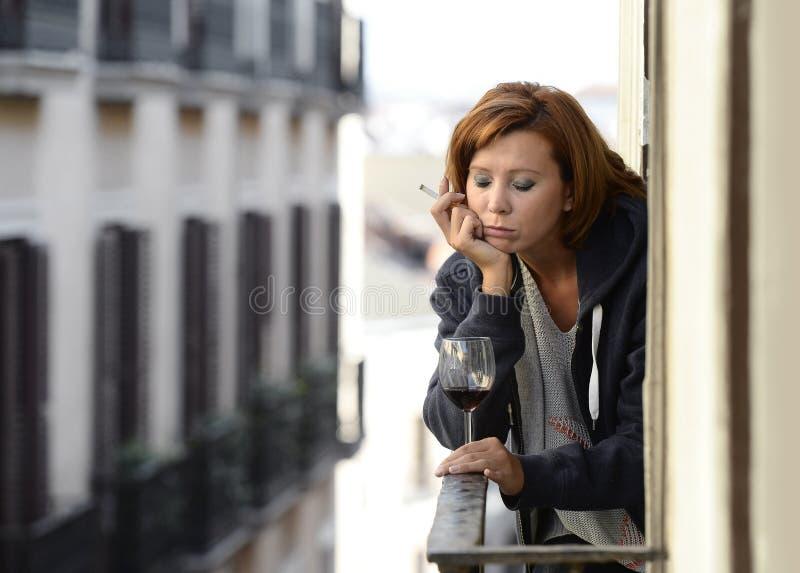 Vrouw die aan depressie en spanning lijden die in openlucht wijn drinken bij het balkon royalty-vrije stock fotografie