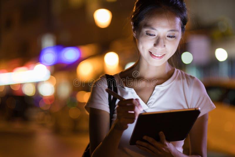 Vrouw die aan digitale tabletcomputer bij nacht werken stock foto