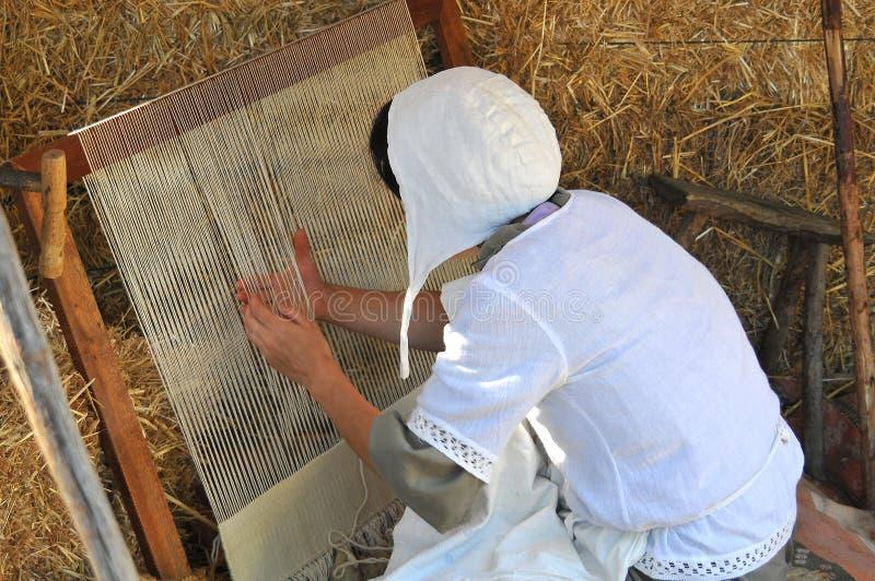 Vrouw die aan een oud weefgetouw werken, de traditie te houden van ambachten en het weven stock foto