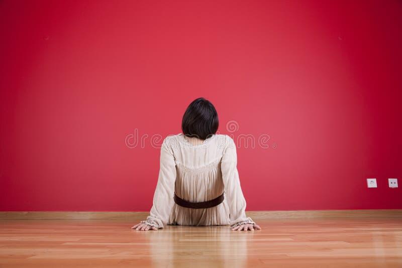 Vrouw die aan een rode muur kijkt stock foto's