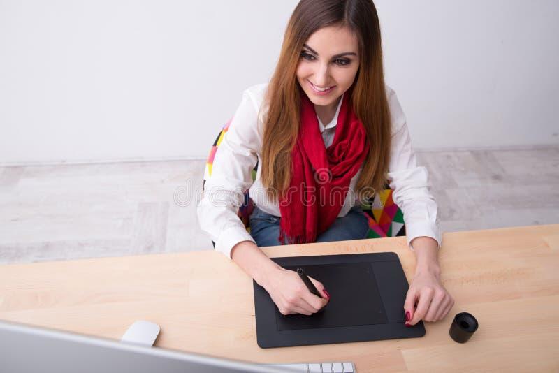 Vrouw die aan grafische tablet in bureau werken stock fotografie