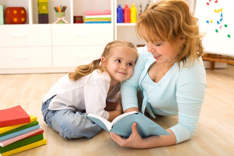 Vrouw die aan haar meisje leest stock afbeeldingen