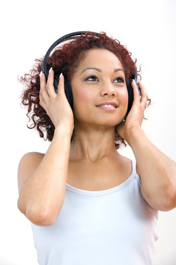 Vrouw die aan hoofdtelefoons luistert stock foto