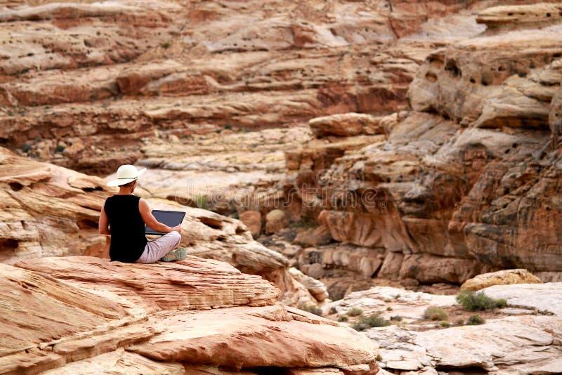 Vrouw die aan laptop computer hoog op rotsen uitwerken stock foto
