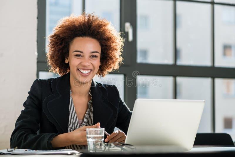 Vrouw die aan laptop in het bureau werkt stock foto's