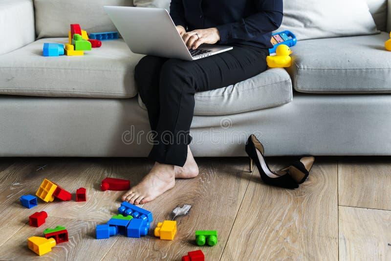 Vrouw die aan laptop op bank werken royalty-vrije stock afbeeldingen