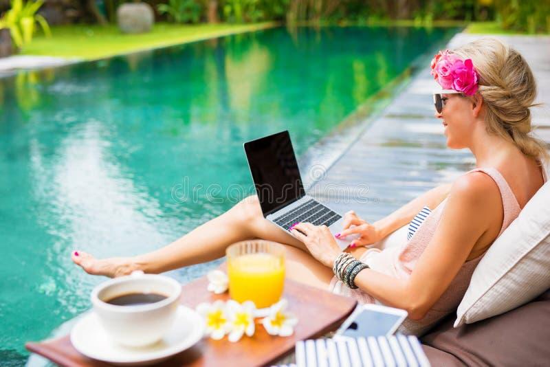 Vrouw die aan laptop werken terwijl het zitten door de pool stock afbeeldingen