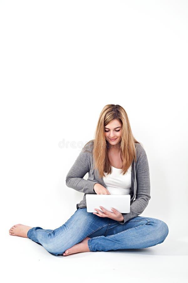 Vrouw die aan laptop werken terwijl het zitten op de vloer stock foto's