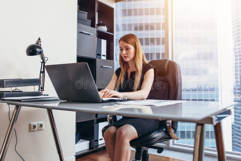 Vrouw die aan laptop zitting bij haar bureau in bureau werken stock afbeelding