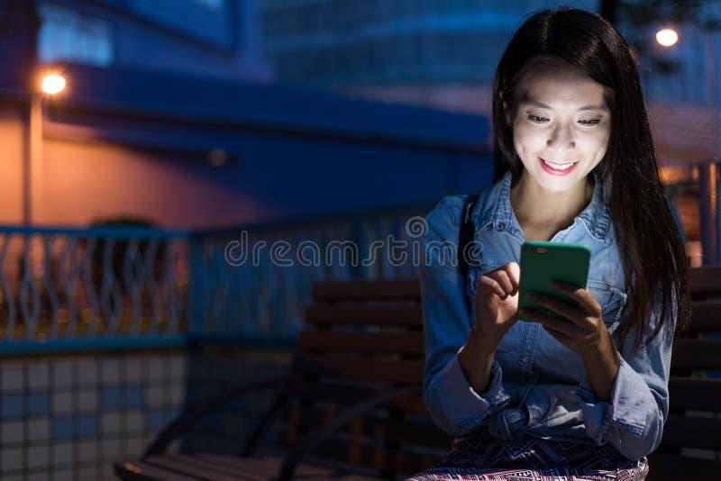 Vrouw die aan mobiele telefoon in de straat werken stock foto