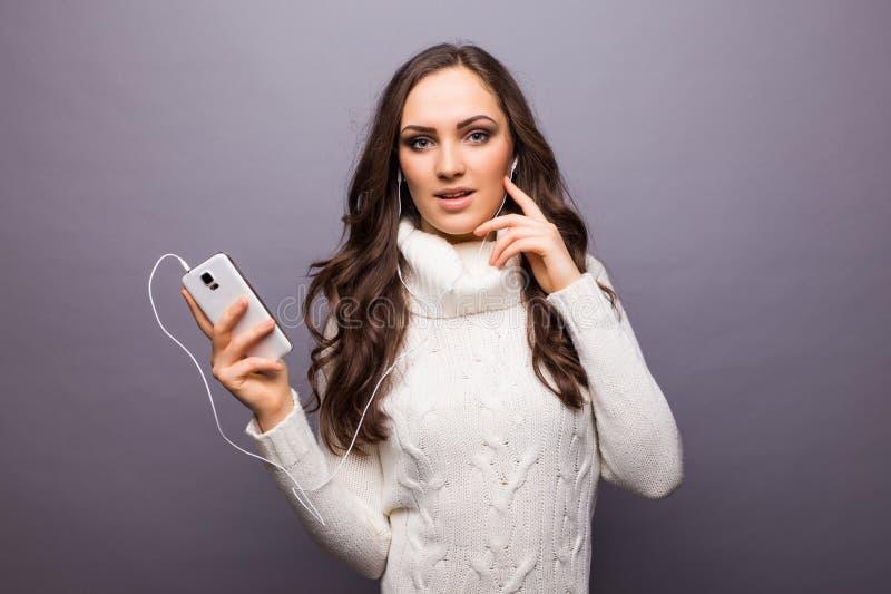 Vrouw die aan muziek dansen die aan telefoon met oortelefoons luisteren stock foto