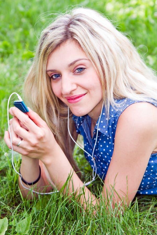 Vrouw die aan muziek luisteren die op het gras liggen stock foto's